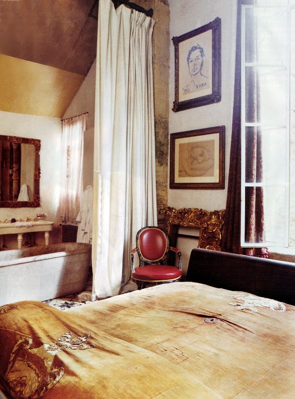 Bathroom in a loft with a stand alone marble tub, floor length curtain, red Louis XIV chair, a bed and framed sketches