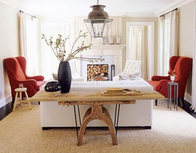 Living room with cream colored walls, dark wood floor, sisal rug, reclaimed wood table, two read armchairs and two tufted white armchairs on each side of a white fireplace