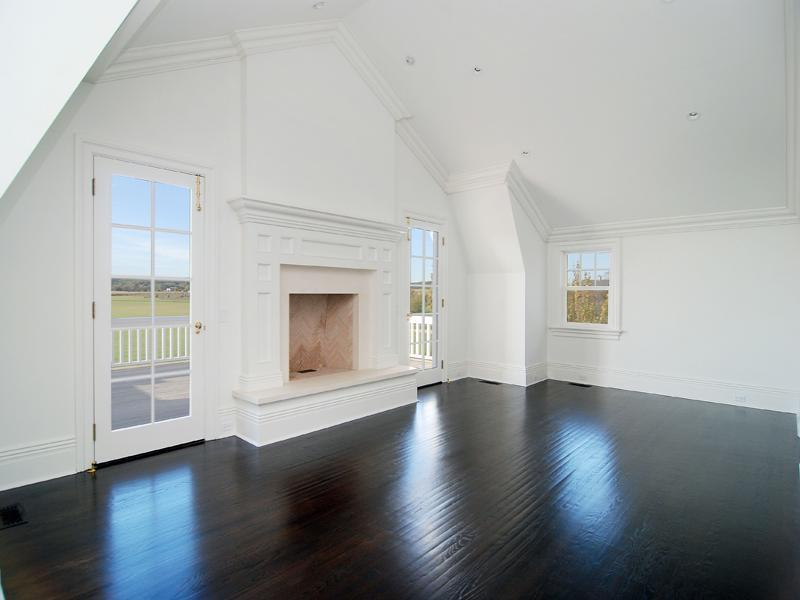 Empty bedroom in a Hamptons farm with dark wood floor, white walls, a fireplace and a door leading to an outdoor patio