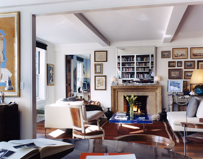 Living room with Yves Klein's Table Bleue, a wood floor, a brick fireplace with a mirror on the mantel, visible beams, and a white sofa with matching armchair