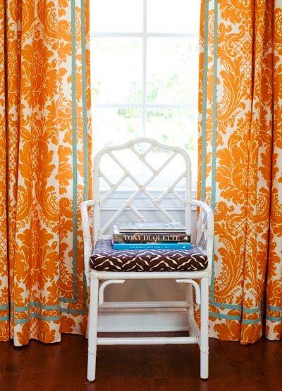 White glossy lacquer faux bamboo armchairs between orange and white brocade curtains in a cherry den