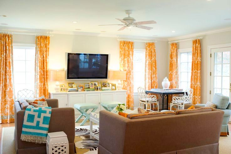 Cherry den with orange and white curtains, brown sofas, light blue armchair with matching x-benches, glossy lacquered faux bamboo armchiars and a zebra rug