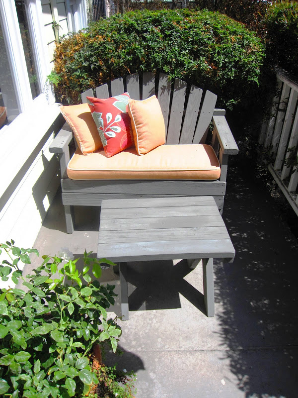 Grey Adirondack love seat with orange seat cushion on a front porch in Venice Beach, CA