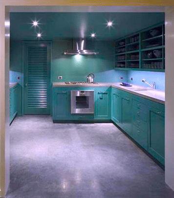Beach house kitchen by Stephan Jaklitsch with custom green cabinetry, open shelving, concrete floors and counter and a built in stainless steel oven