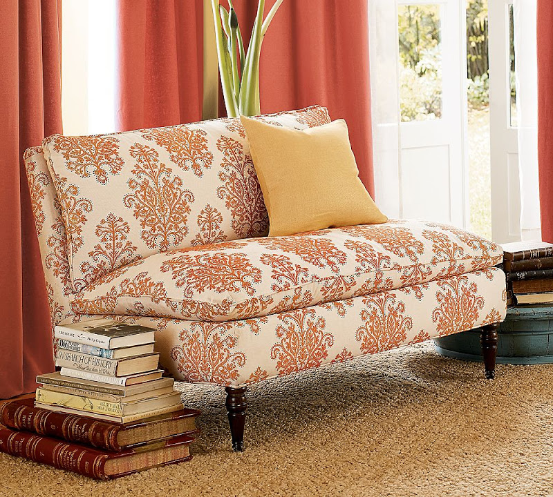 Armless loveseat upholstered in orange and white damask fabric from Pottery Barn