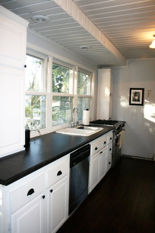 Angela of Fixing it Fancy's kitchen after her remodeling with white cabinets and drawers, walnut floor and stainless appliances