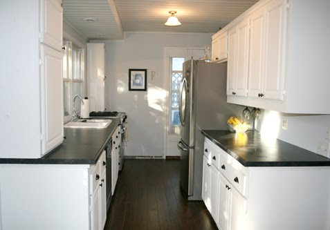 Kitchen in Angela of Fixing it Fancy's home with white cabinets and drawers, dark wood floor and black countertops