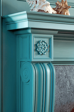 Detail of carved woodwork on a fireplace mantel in a blue library designed by Peter Pennoyer