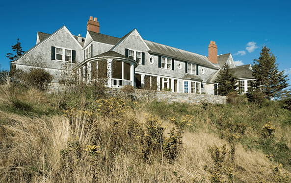 Traditional exterior of an East Coast waterfront home with gray shingle siding, black shutters and white trim by Peter Pennoyer