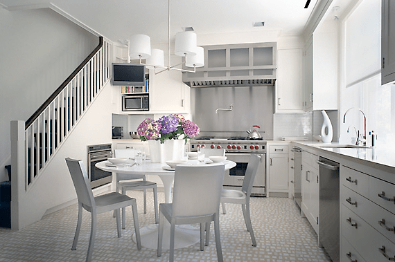 White eat in kitchen designed by Peter Pennoyer with white tile floor and stainless appliances
