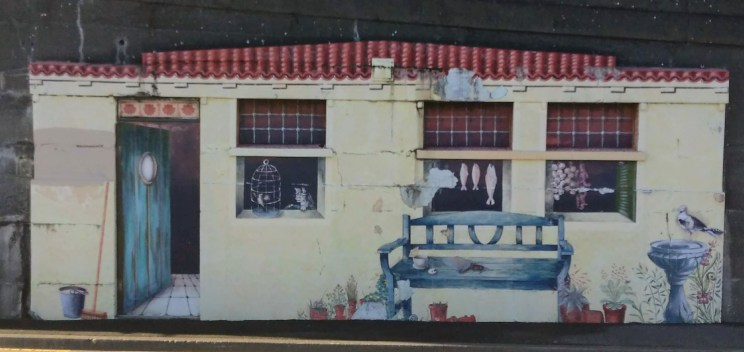Mural showing the windows of a house with door open - at Wellington