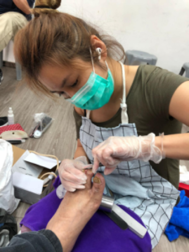 Cass Ng trims a senior citizen's toenails at HKL3C Life Commitment Charity Club. Photo: Supplied