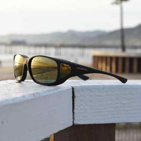 Cocoons fitover sunglasses in gold mirror at the beach
