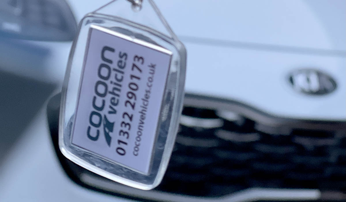 Cocoon Vehicles Keyring in front of a Kia Sportage