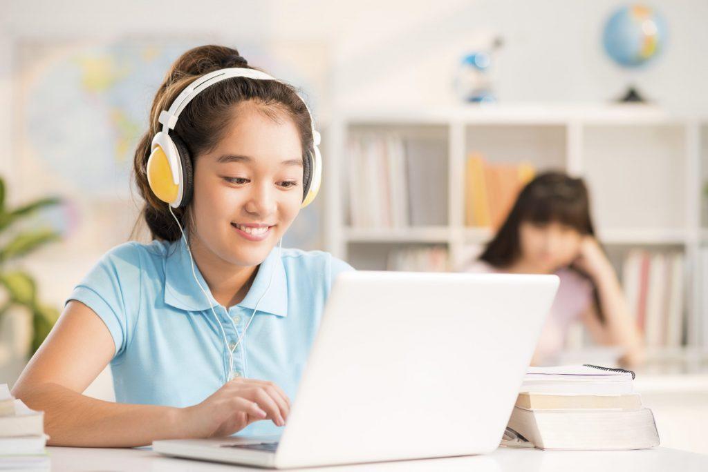 Vietnamese schoolgirl with headphones using laptop in the class