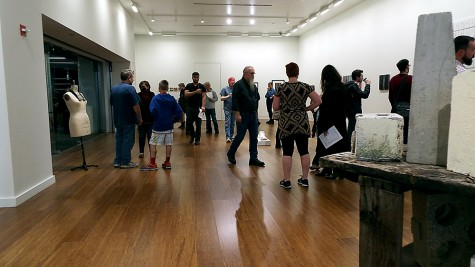 A group of people viewing the Faculty Art Exhibit at College of DuPage on Nov, 6, 2014. The art exhibit displayed multiple different art forms, from paintings to sculptures.