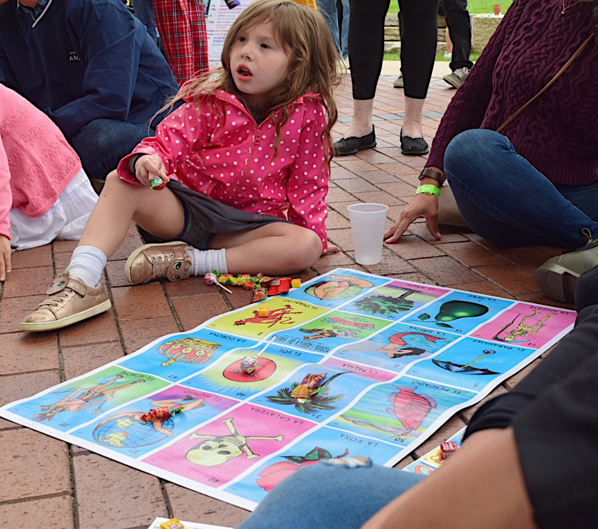 Young+girl+sits+with+candy+and+a+classic+board+game%2C+La+Loteria.