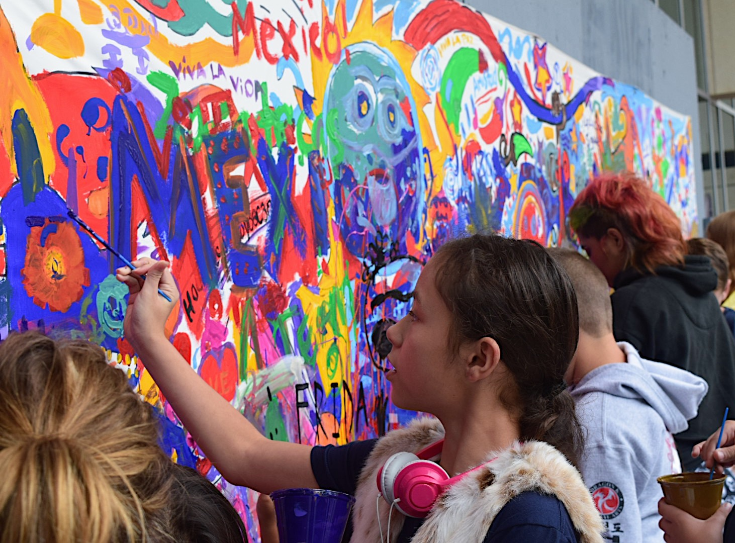 Adults+and+children+alike+gathering+to+contribute+to+the+community+mural.