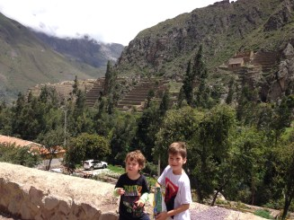 You can barely see the Ollantaytambo ruins in the distance behind the boys
