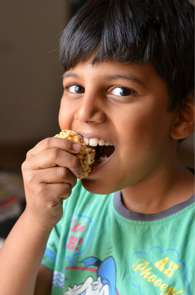 my son eating a bite from the murmura laddo