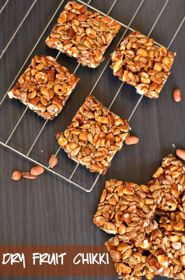dry fruit chikki or mixed nut brittle bar is placed on rack, close up from above. Peanuts are scattered around.