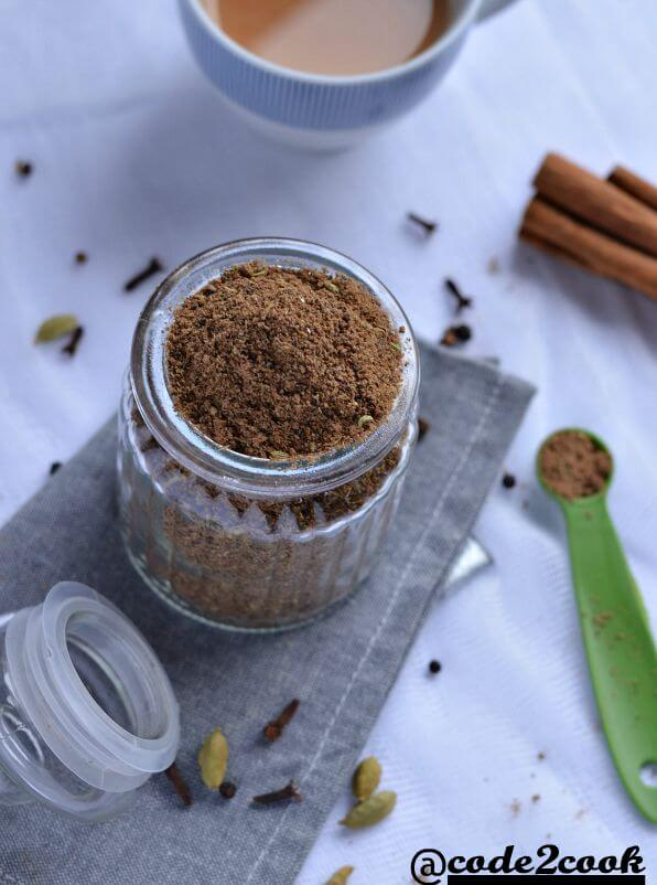 homemade masala chai spice mix is shown in glass jar, surrounded by whole spices. Photo is taken from top.
