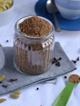 masala chai mix or chai ka masala kept in glass jar, whole spices are scattered around it. Photo is taken from top.