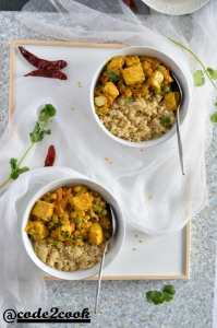 manipuri traditional vegan paneer thongba served with quinoa in two bowls. Ariel click with two bowls on a serving tray.