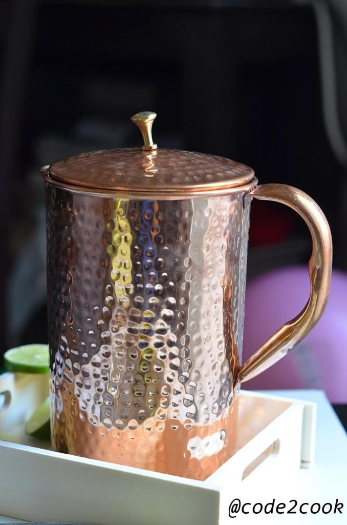 copper pitcher is kept in wooden tray with lid