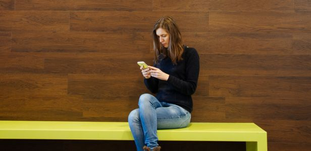Photo of Evangelia sitting on a bench in Freeagent's office
