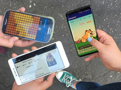 Three hands holding smartphones that display Android apps