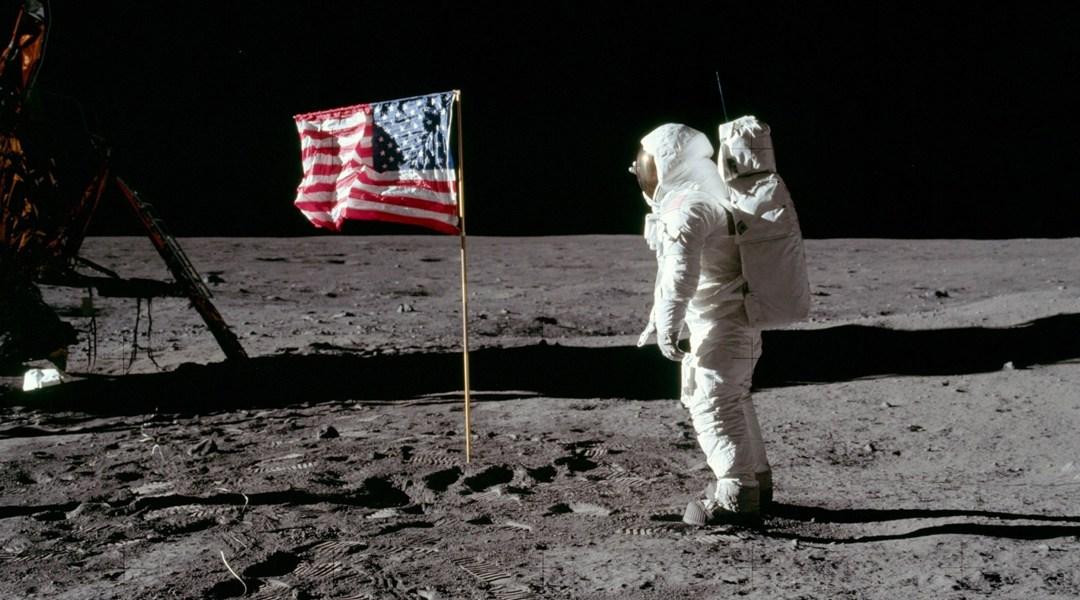 Astronauta en la luna frente a bandera norteamericana