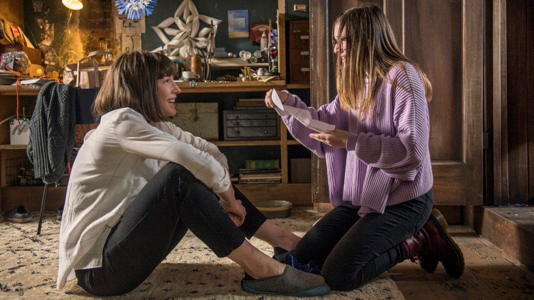 Mujer sentada en el suelo platicando con una niña que está de rodillas