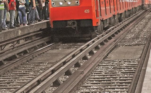 Vías del metro de la ciudad de mexico tren anaranjado en el fondo