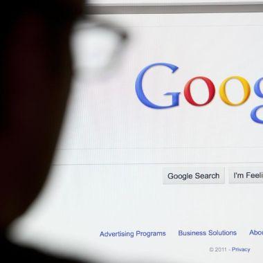 Hombre sentado frente a computadora logo Google
