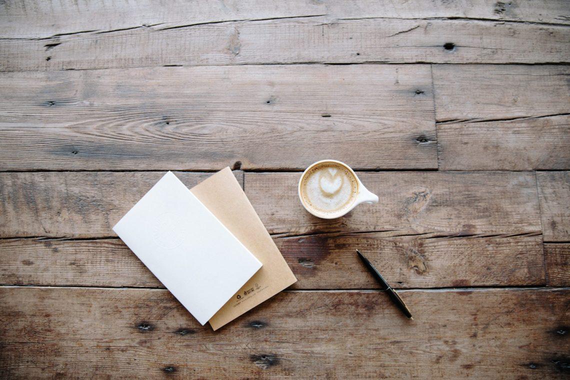 Une petite tasse sur une table en bois avec des cahiers