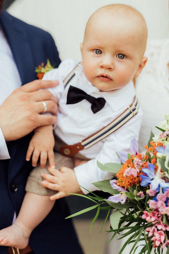 Sohn vom Brautpaar, auf dem Arm von Papa. Herausgeputzt mit Fliege und Hosenträgern für die Hochzeit seiner Eltern.