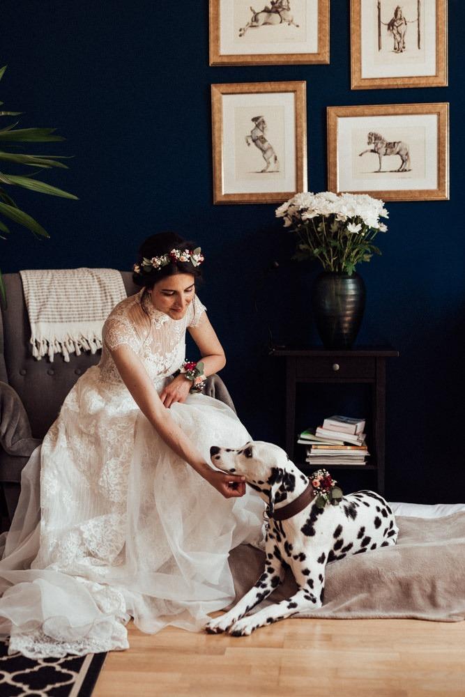 Braut mit Blumenkranz sitzt auf einem gemütlichen Ohrensessel, an ihren Füßen liegt ihr Dalmatiner.