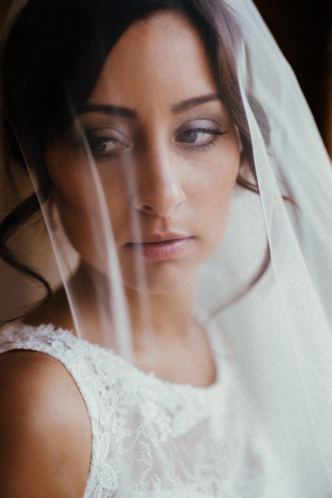 Portrait einer italienischen Braut. Sie schaut verträumt unter ihrem Schleier hervor.