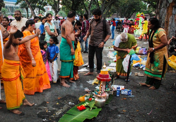 Indian boy making offering to Muruga during Blessing woman in sari during Thaipusam in Penang