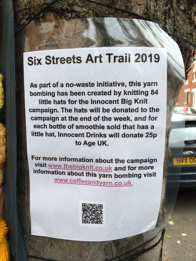 A picture showing a laminated A4 sheet of paper containing information about the yarn bombing and a QR code linking to this blog post