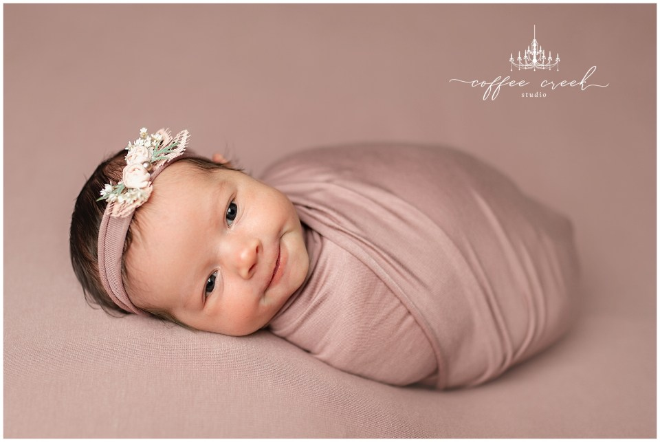 newborn photographer session baby girl in pink wrap eyes open