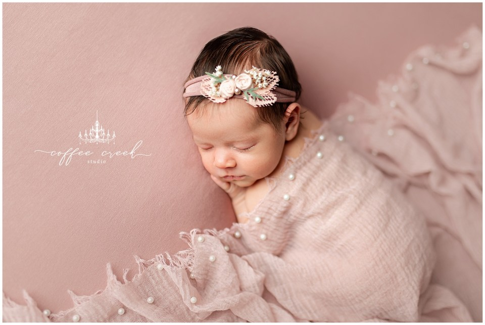 newborn photographer session baby girl in pink wrap with headband