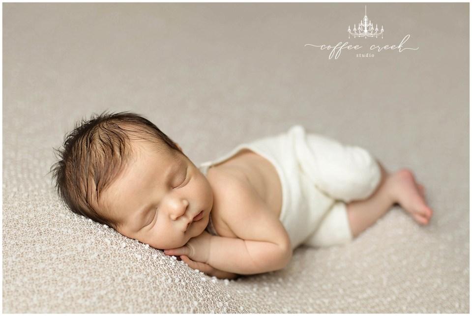 newborn baby boy asleep on overalls