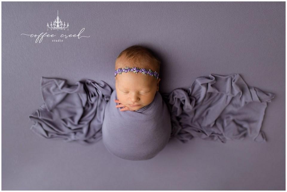 newborn baby girl in purple blanket
