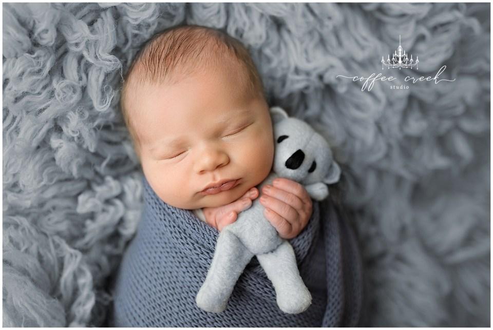 newborn baby boy with bear stuffy