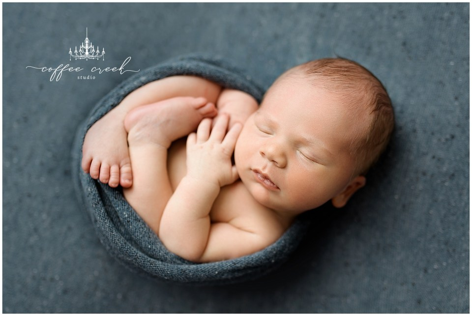 newborn baby boy posed in wrap on blue