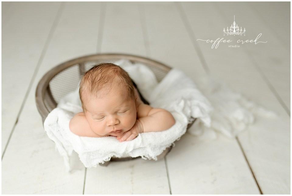 newborn baby boy posed in basket