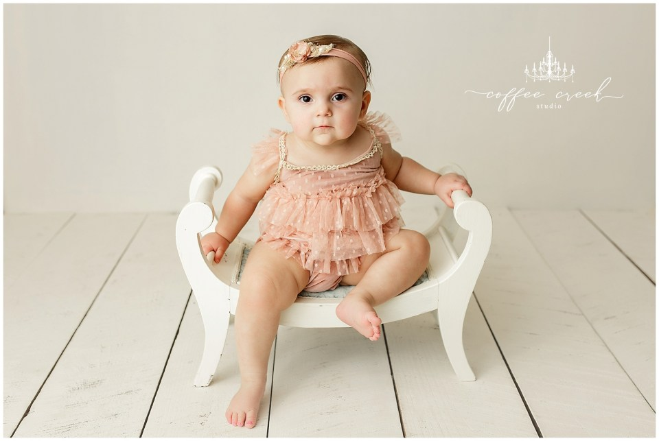 baby girl in pink on white bench
