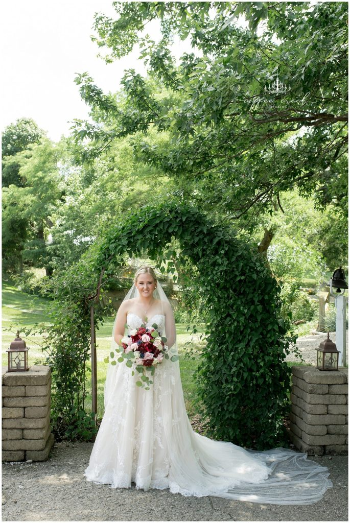 bride in wedding dress under green archway